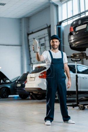 Photo pour Mécanicien heureux de voiture dans la bouteille de fixation de chapeau avec l'huile de voiture tout en restant dans le service de voiture - image libre de droit