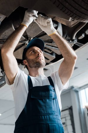 Photo for Low angle view of handsome car mechanic repairing automobile in car service - Royalty Free Image