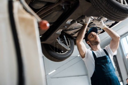 Photo for Selective focus of bearded car mechanic repairing automobile in car service - Royalty Free Image