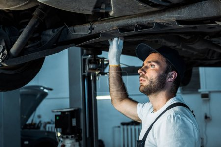 Photo for Bearded car mechanic in cap repairing automobile in car service - Royalty Free Image