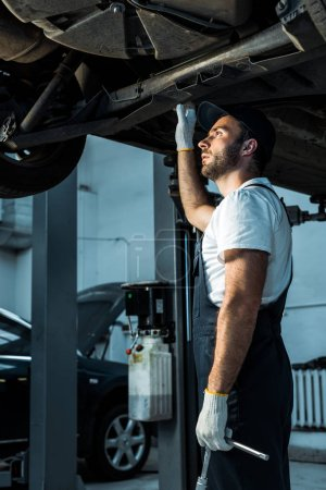 Photo for Bearded car mechanic in cap standing near automobile in car service - Royalty Free Image