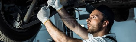 Photo for Panoramic shot of  bearded car mechanic in cap repairing automobile in car service - Royalty Free Image