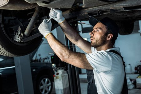 Photo for Bearded auto mechanic in cap repairing automobile in car service - Royalty Free Image