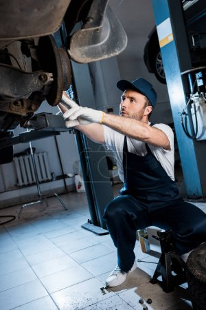 Photo for Bearded auto mechanic in cap and gloves repairing automobile in car service - Royalty Free Image