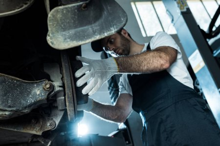 Photo for Low angle view of auto mechanic in cap and gloves repairing automobile in car service - Royalty Free Image