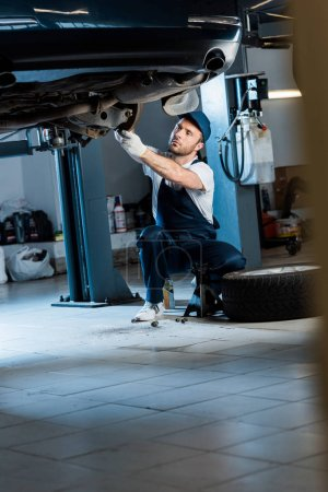 Photo for Handsome auto mechanic in cap repairing car in car service - Royalty Free Image