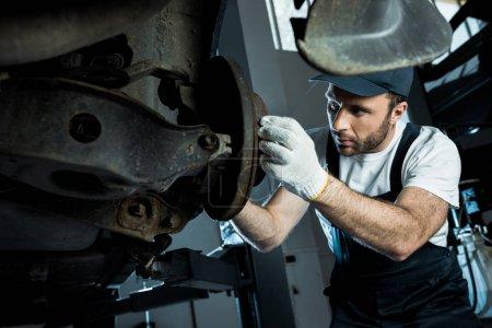Photo pour Mise au point sélective de mécanicien automatique dans le chapeau et les gants réparant l'automobile dans le service de voiture - image libre de droit