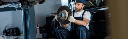 Photo for Panoramic shot of handsome car mechanic looking at metallic car brake - Royalty Free Image
