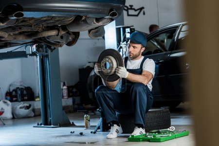 Photo for Selective focus of handsome car mechanic looking at metallic car brake - Royalty Free Image