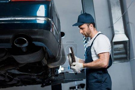 Photo pour Foyer sélectif du mécanicien de voiture beau retenant le détail métallique près de l'automobile - image libre de droit