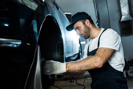 Photo for Selective focus of car mechanic repairing automobile in car service - Royalty Free Image