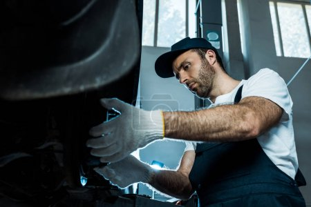 Photo for Selective focus of handsome auto mechanic working in car service - Royalty Free Image