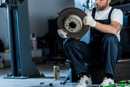 Photo for Cropped view of car mechanic holding metallic car brake while sitting on car tire - Royalty Free Image