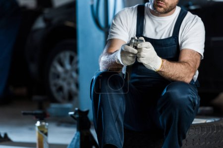 Photo for Cropped view of car mechanic holding metallic tool while sitting on car tire - Royalty Free Image