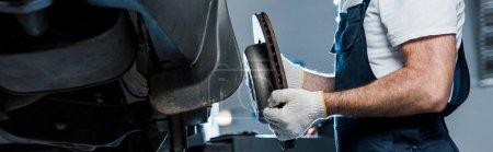 Photo for Panoramic shot of car mechanic holding metallic car brake near automobile - Royalty Free Image
