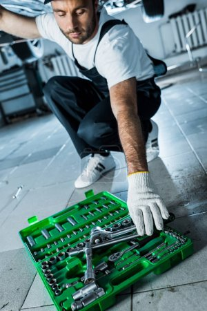 Photo for Selective focus of auto mechanic taking metallic tool from toolbox - Royalty Free Image
