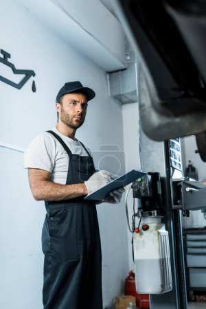 Photo for Selective focus of auto mechanic holding clipboard while looking at car - Royalty Free Image