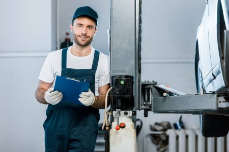 Photo for Cheerful auto mechanic in cap holding clipboard in car service - Royalty Free Image