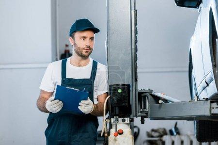 Photo pour Barbu mécanicien automobile en chapeau regardant la voiture et tenant presse-papiers dans le service de voiture - image libre de droit
