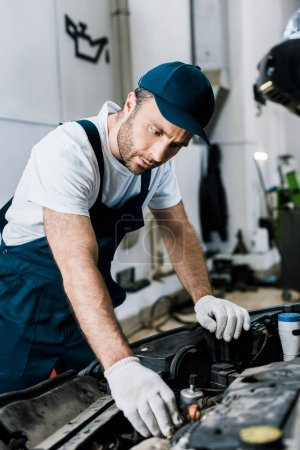Photo for Selective focus of repairman in gloves looking at car engine - Royalty Free Image
