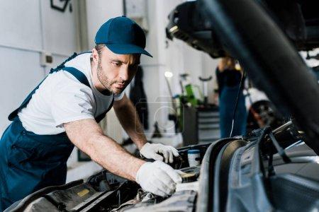 Photo pour Focus sélectif de mécanicien de voiture barbu dans les gants fixant l'automobile - image libre de droit