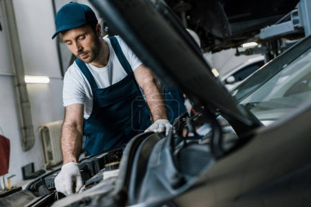 Photo for Selective focus of handsome car mechanic in gloves looking at car engine - Royalty Free Image