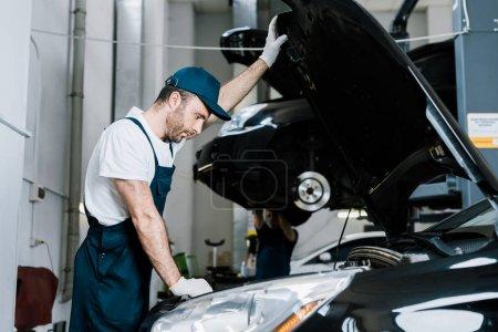 foyer sélectif du mécanicien de voiture barbu dans les gants regardant le moteur de voiture