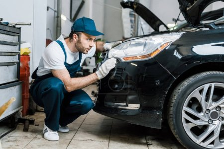 Photo for Handsome car mechanic looking at tail light in black car - Royalty Free Image
