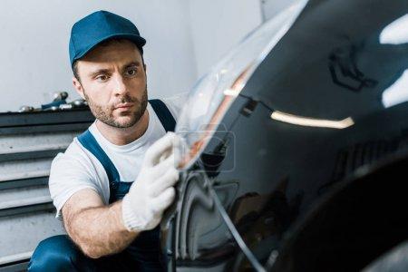 Photo pour Foyer sélectif du beau mécanicien barbu de voiture regardant le feu arrière dans la voiture noire - image libre de droit