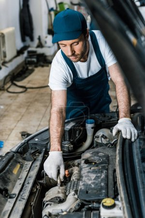 Photo for Selective focus of handsome car mechanic fixing auto in car service - Royalty Free Image