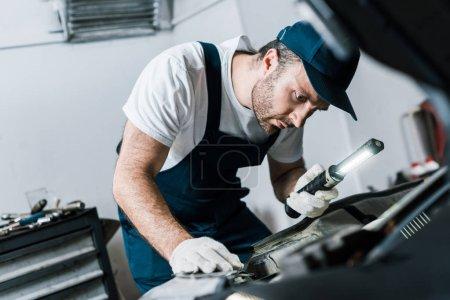 Photo pour Foyer sélectif du mécanicien de voiture barbu tenant lampe de poche près du wagon - image libre de droit