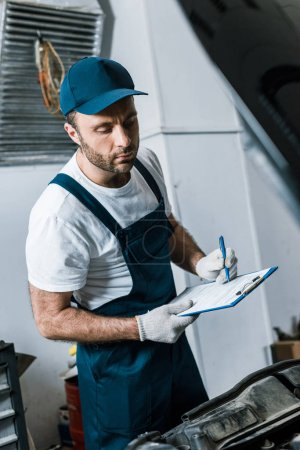 Photo for Selective focus of handsome repairman in cap holding pen and clipboard  near car - Royalty Free Image