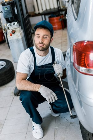 Photo for Selective focus of bearded car mechanic in uniform holding metallic wrench near car - Royalty Free Image