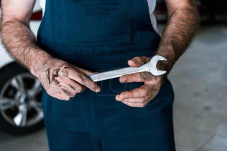 Photo for Cropped view of auto mechanic with mud on hands holding hand wrench in car repair station - Royalty Free Image