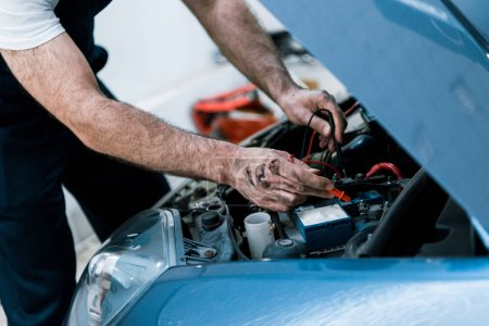 Photo for Cropped view auto mechanic with mud on hands fixing automobile in car repair station - Royalty Free Image