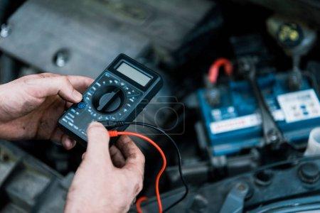 Photo pour Vue recadrée du dispositif de mesure de maintien du mécanicien de voiture en service - image libre de droit