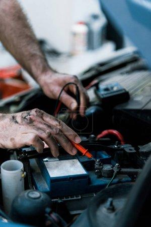 Photo pour Vue recadrée du mécanicien de voiture travaillant dans le service de voiture - image libre de droit