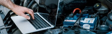 Photo for Panoramic shot of car mechanic using laptop with blank screen near car - Royalty Free Image