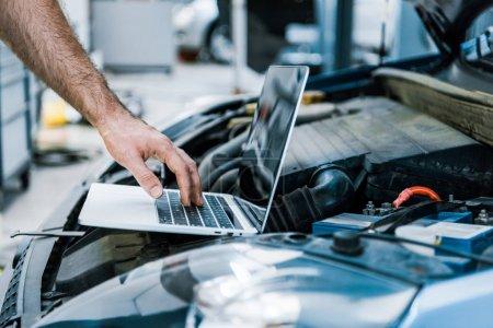Photo pour Vue recadrée de mécanicien automatique à l'aide d'un ordinateur portable avec écran vide près de la voiture - image libre de droit
