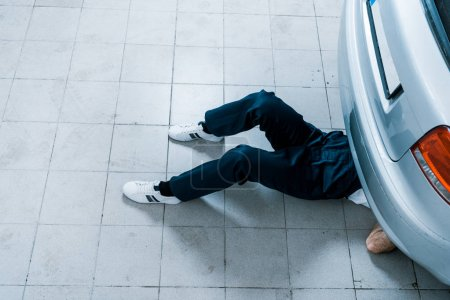 Photo for Overhead view of auto mechanic fixing car in car service - Royalty Free Image