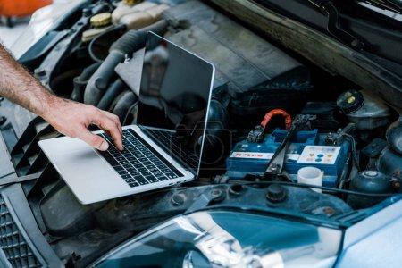 Photo pour Vue recadrée du mécanicien de voiture utilisant l'ordinateur portatif avec l'écran blanc près de la voiture - image libre de droit
