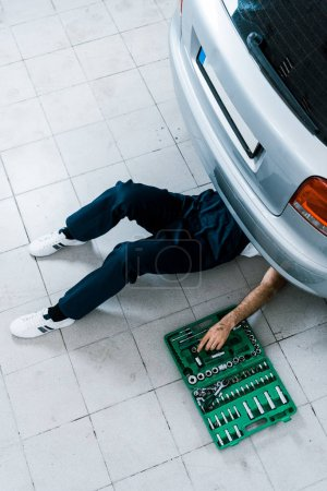 Photo for Overhead view of auto mechanic repairing car in car service - Royalty Free Image