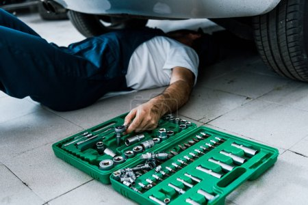 Photo for Cropped view of car mechanic repairing car in car service - Royalty Free Image