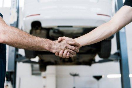 Photo pour Vue recadrée de mécanicien de voiture se serrant la main avec l'homme dans le garage - image libre de droit