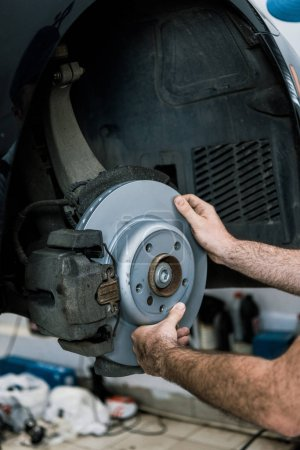 Photo for Cropped view of auto mechanic holding metallic car brake near automobile - Royalty Free Image