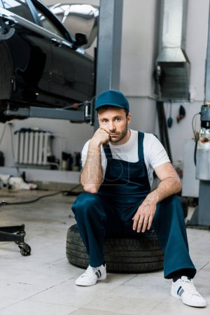 Photo for Upset bearded man looking at camera and sitting on car tire - Royalty Free Image