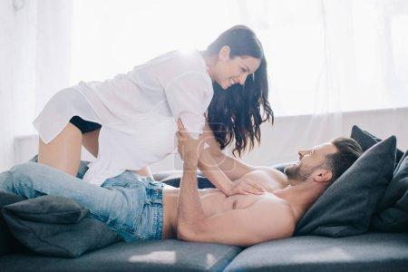 Photo pour Femme attirante et brune dans la chemise étreignant avec l'homme torse nu sur le sofa - image libre de droit