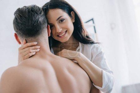 Foto de Mujer atractiva y morena en camisa abrazando con hombre sin camisa - Imagen libre de derechos