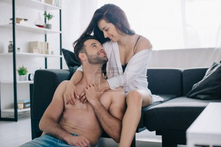 Photo for Attractive and smiling woman in shirt hugging with handsome and shirtless man - Royalty Free Image