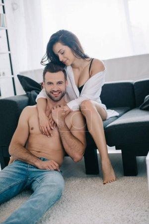 Photo pour Femme attirante et souriante dans la chemise étreignant avec l'homme torse nu et beau - image libre de droit